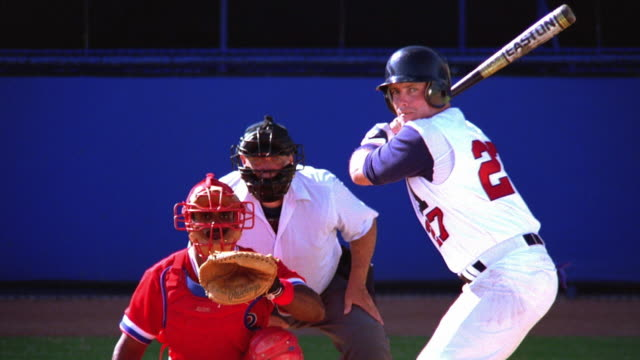 medium shot zoom in baseball player swinging and hitting ball while batting with catcher + umpire in background - baseballspieler stock-videos und b-roll-filmmaterial
