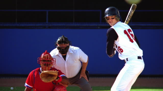 Medium shot zoom in baseball player swinging and missing ball while batting with catcher + umpire in background