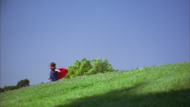 Medium shot zoom in boy in red superhero cape standing and turning on hillside