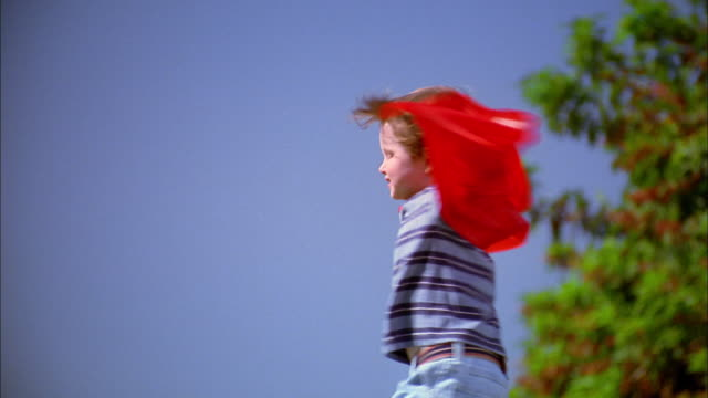 Medium shot zoom in boy in red superhero cape turning w/cape blowing in wind