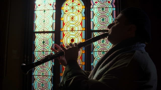 vidéos et rushes de medium shot zoom in clarinetist plays in profile w/stained glass windows in background - judaism