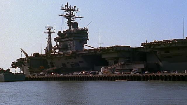 Medium shot zoom in docked aircraft carrier / Norfolk, Virginia