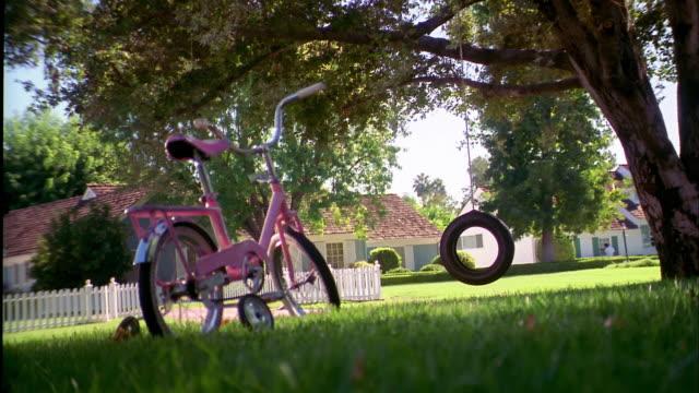 vídeos de stock e filmes b-roll de medium shot zoom in empty tire swing swinging in yard w/young girl's bicycle in foreground - baloiço