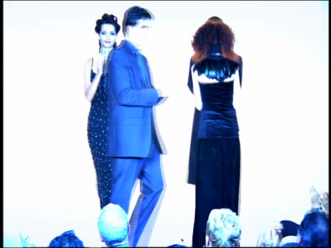 Medium shot zoom in male and female models walk on catwalk clapping then bring out designer who waves to audience