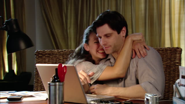 Medium shot zoom in man and woman looking at laptop together / woman hugging man