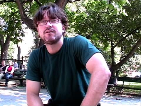 stockvideo's en b-roll-footage met medium shot zoom in man sitting in park rolling his tongue for camera/ new york city - alleen mid volwassen mannen