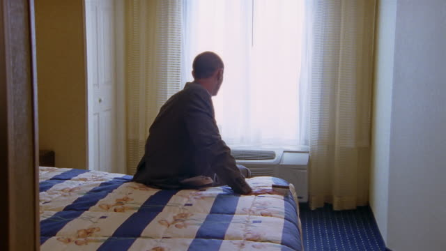 medium shot zoom in man sitting on bed in hotel room looking out window and turning around - one person stock videos & royalty-free footage