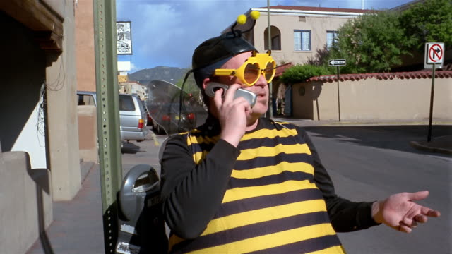 Medium shot zoom in man wearing bee costume talking on cell phone