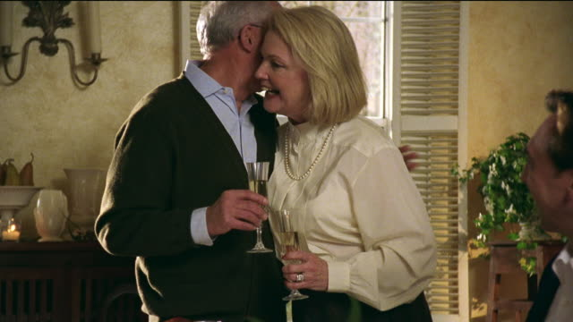 Medium shot zoom in mature couple holding champagne glasses and kissing as they stand at dinner table