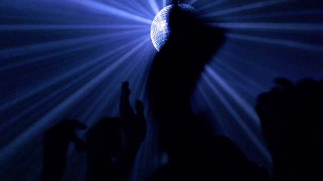 Medium shot zoom in mirror ball spinning and reflecting blue light rays with arms of dancers raised in nightclub