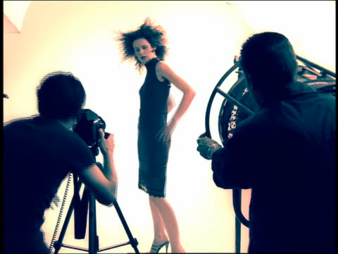 Medium shot zoom in model posing in studio for photographer and fan operator in foreground