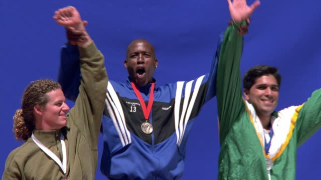 Medium shot zoom in pan three male athletes with medals celebrating on victory stand