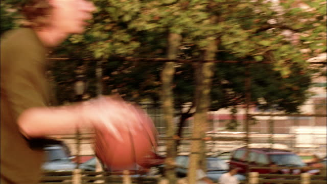 medium shot zoom in pan young men playing basketball at martin f. tenahey playground / new york city - 30 seconds or greater stock videos & royalty-free footage