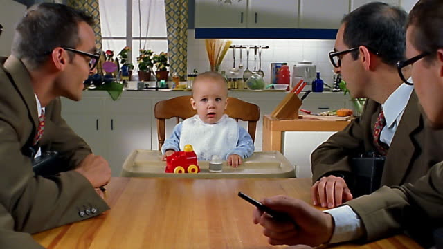 medium shot zoom in past businessmen to smiling baby in high chair - market research stock videos and b-roll footage