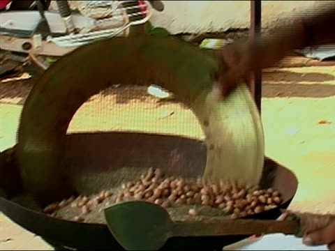 medium shot zoom in peanut-wallah roasting nuts at outdoor stand during thrissur pooram elephant festival / thrissur, kerala, india - peanut food stock videos & royalty-free footage