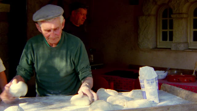 medium shot zoom in senior man kneading and shaping dough outdoors with other senior men in background / provence, france - french bakery stock videos & royalty-free footage