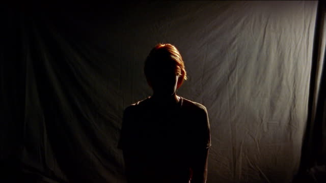 medium shot zoom in silhouetted woman - controluce video stock e b–roll