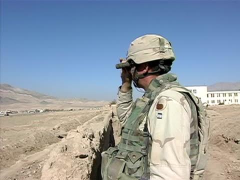 vidéos et rushes de medium shot zoom in soldier looking at landscape through binoculars/ afghanistan - opération enduring freedom