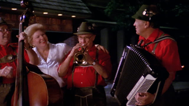 1990 medium shot zoom in three members of german folklore band and singer performing outside restaurant / columbus - anno 1990 video stock e b–roll