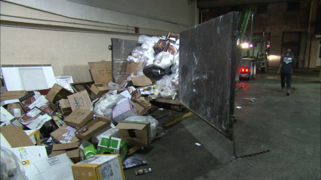 stockvideo's en b-roll-footage met medium shot zoom in tilt down - trash bags and cardboard boxes spilling out of a garbage container / new orleans louisiana - afvalcontainer container