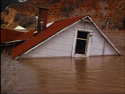 vidéos et rushes de 1986 medium shot zoom in toward roof window of house submerged under water during flood / audio - force de la nature