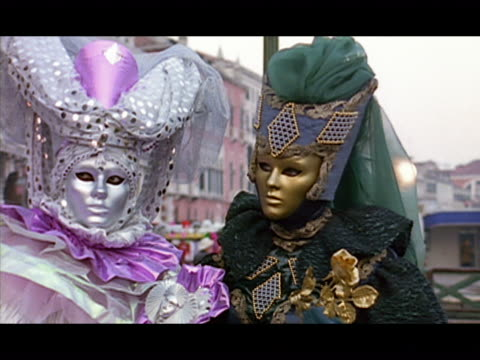medium shot zoom in two people wearing carnivale masks and costumes and looking around / venice, italy - 17th century style stock videos & royalty-free footage