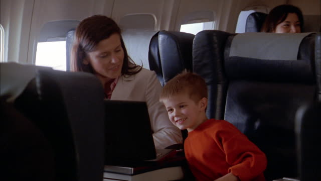 Medium shot zoom in woman and young boy looking at laptop computer on airplane