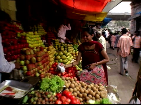Medium shot zoom in woman buying produce at fruit stand at market / vendor giving her change