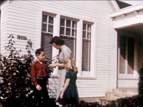 stockvideo's en b-roll-footage met 1954 medium shot zoom in woman walking with boy and girl / giving boy money and bending down to talk to girl / audio - zus