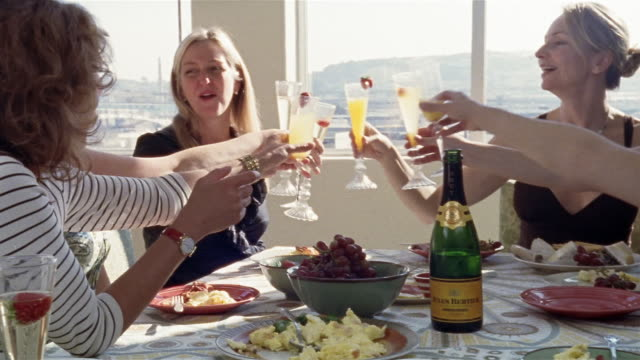 medium shot zoom in women making champagne toast at brunch table/ san francisco, california - brunch stock videos & royalty-free footage