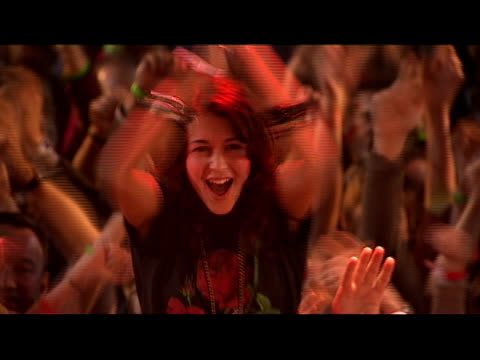 vidéos et rushes de medium shot zoom in young woman clapping and sitting on man's shoulders amongst crowd at concert/ zoom out woman and crowd/ london, england - bras humain