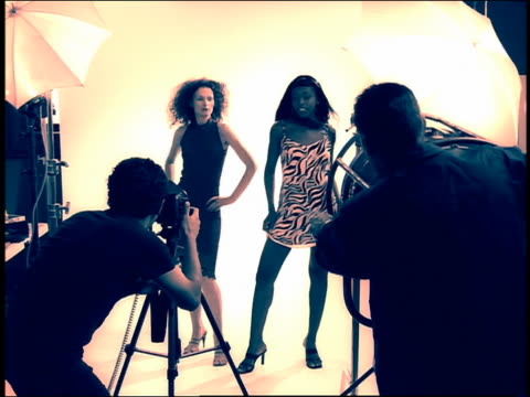 Medium shot zoom in zoom out Black model and redheaded model posing in studio for photographer + fan operator in foreground