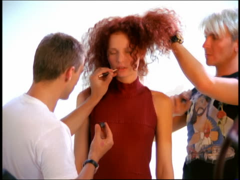 medium shot zoom in zoom out hairdresser and makeup artist working on model in studio with photographer + fan operator in foreground - photo shoot stock videos & royalty-free footage