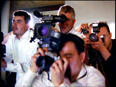 vídeos de stock e filmes b-roll de medium shot zoom in zoom out male photographers and video cameraman working indoors with glare from lights at fashion show - fotógrafo