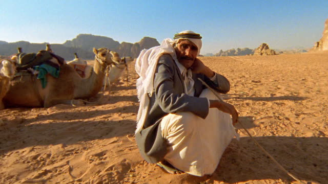 medium shot zoom in zoom out middle age middle eastern (bedouin) man sitting in wadi rum desert with camels in background / jordan - camel stock videos & royalty-free footage
