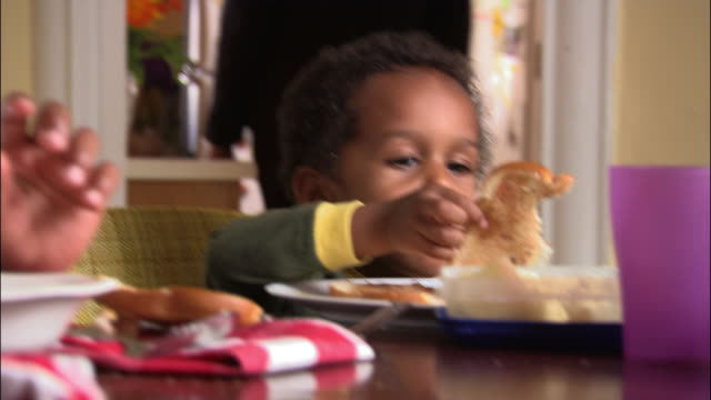 medium shot zoom in zoom out toddler eating breakfast in dining room/ mother bring plastic container of cereal into room - plastic container stock videos and b-roll footage