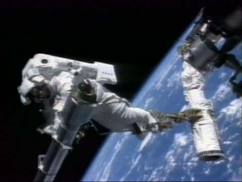 Medium shot zoom out astronauts installing equipment on the International Space Station