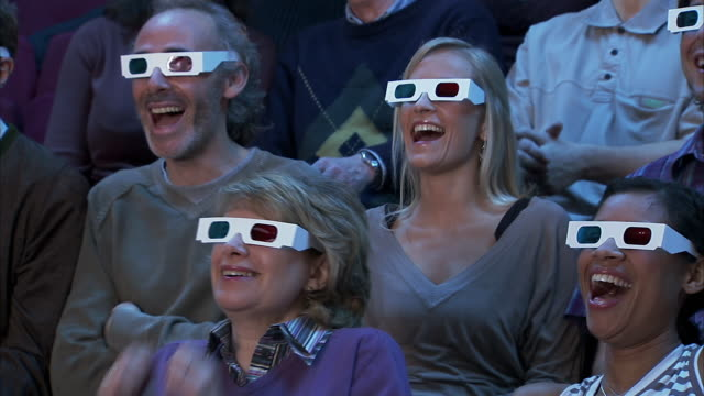 Medium shot zoom out audience wearing 3-D glasses reacting to movie out of frame with shock and pleasure