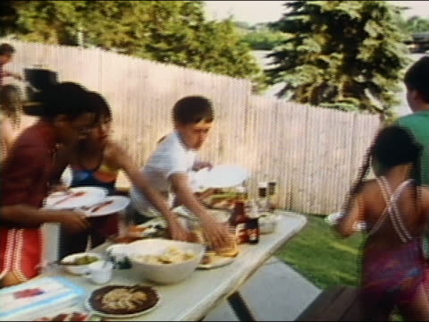 1986 medium shot zoom out boys and girls making plates of food at backyard barbecue / audio - swimwear videos stock videos and b-roll footage