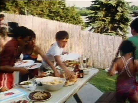 1986 medium shot zoom out boys and girls making plates of food at backyard barbecue / audio - hamburger stock videos & royalty-free footage