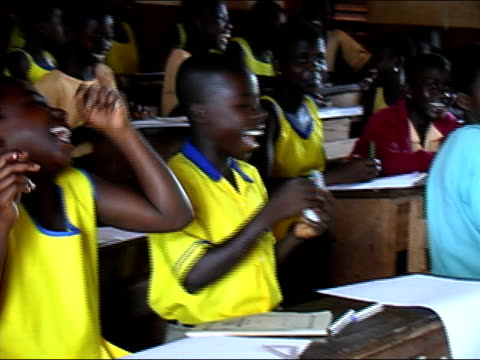 Medium shot zoom out children laughing in classroom/ Ghana