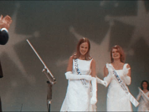 1970 medium shot zoom out contestants hugging junior miss arizona / winner receiving sash flowers and tiara - america's junior miss stock videos & royalty-free footage
