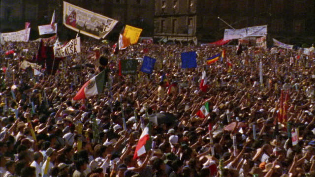 vidéos et rushes de medium shot zoom out crowds of people celebrating on main square / zoom in mexican flag / mexico city - 1990 1999