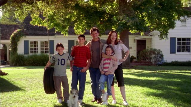 medium shot zoom out family w/dog posing by tire swing in front yard of suburban house - partire bildbanksvideor och videomaterial från bakom kulisserna