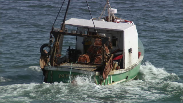 medium shot zoom out fishing boat dropping lobster traps in north sea near arbroath cliffs/ aberdeenshire, scotland - north sea stock videos & royalty-free footage