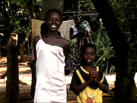 Medium shot zoom out group of children standing in wooded area/ Ghana