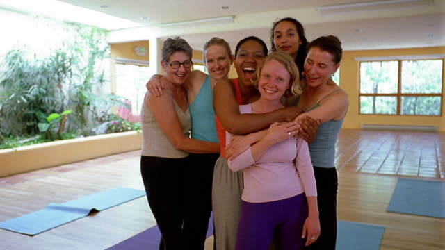 Medium shot zoom out group of women in leotards embracing and smiling in yoga studio