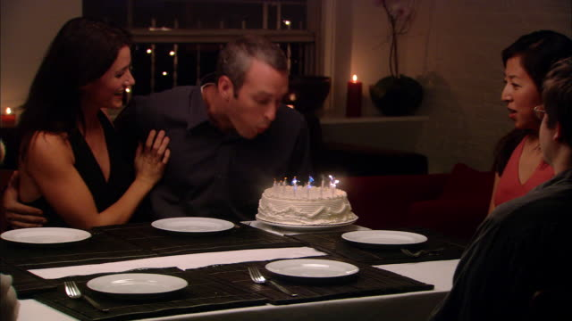 vidéos et rushes de medium shot zoom out man blowing out candles on birthday cake as people around table clap - couple d'âge moyen