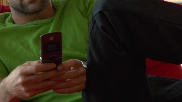 stockvideo's en b-roll-footage met medium shot zoom out man text messaging/ new jersey - hanenkam haardracht