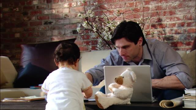 stockvideo's en b-roll-footage met medium shot zoom out man working at laptop in living room / baby playing at coffee table - multitasken